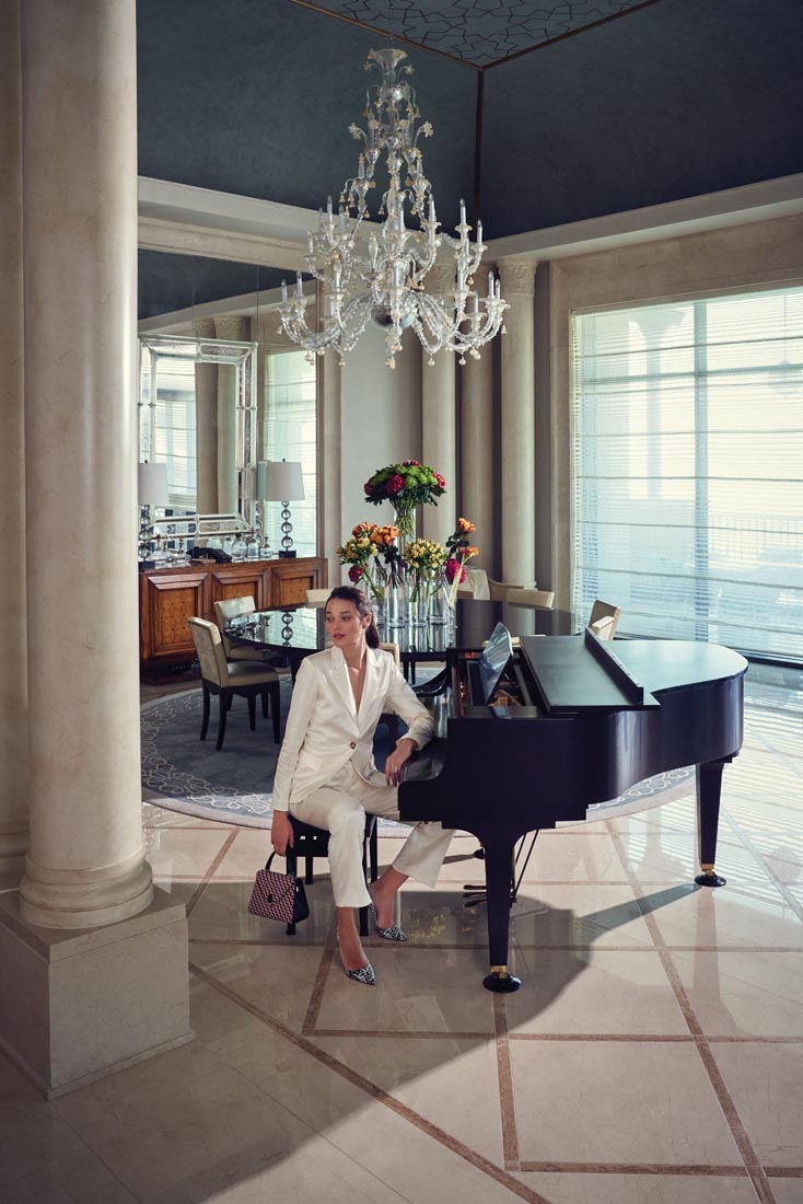A baby grand piano takes centre stage in the suite's palatial living area. Suit, Zendaya x Tommy Hilfiger Heels, Christian Louboutin Bag, Valextra Ring, Givenchy