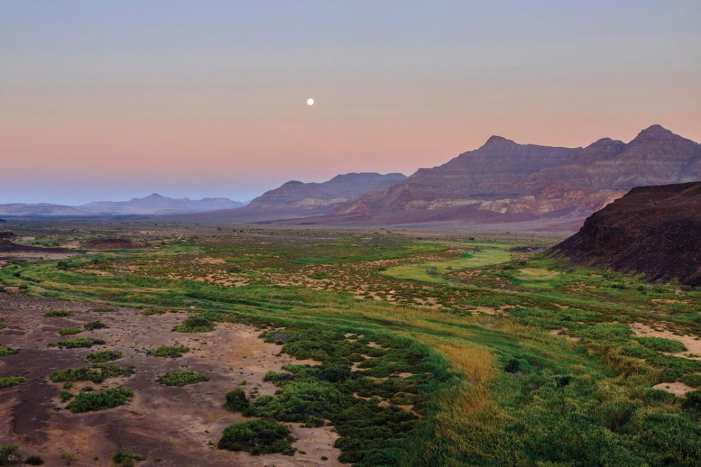 Moon rising over a dry river valley in Namibia