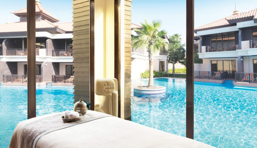 View of villas and blue pool with palm tree in centre from the spa treatment room at Anantara The Palm Dubai