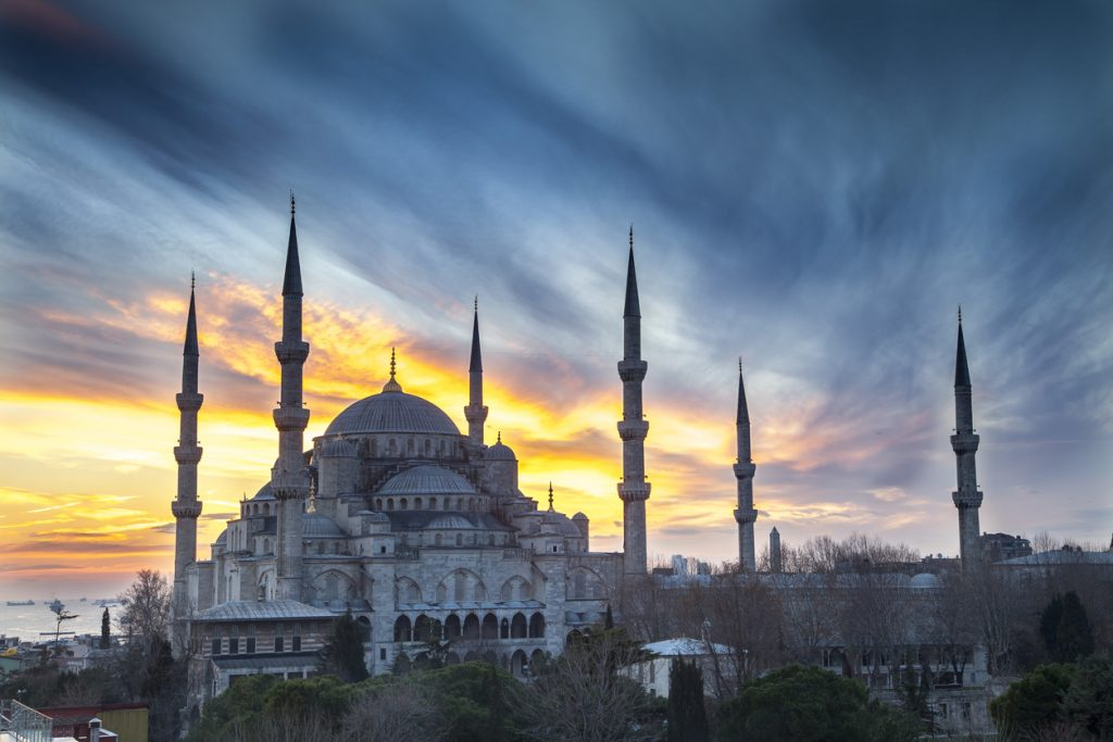 The Blue Mosque in Istanbul set against a fiery sunset and cloudy sky