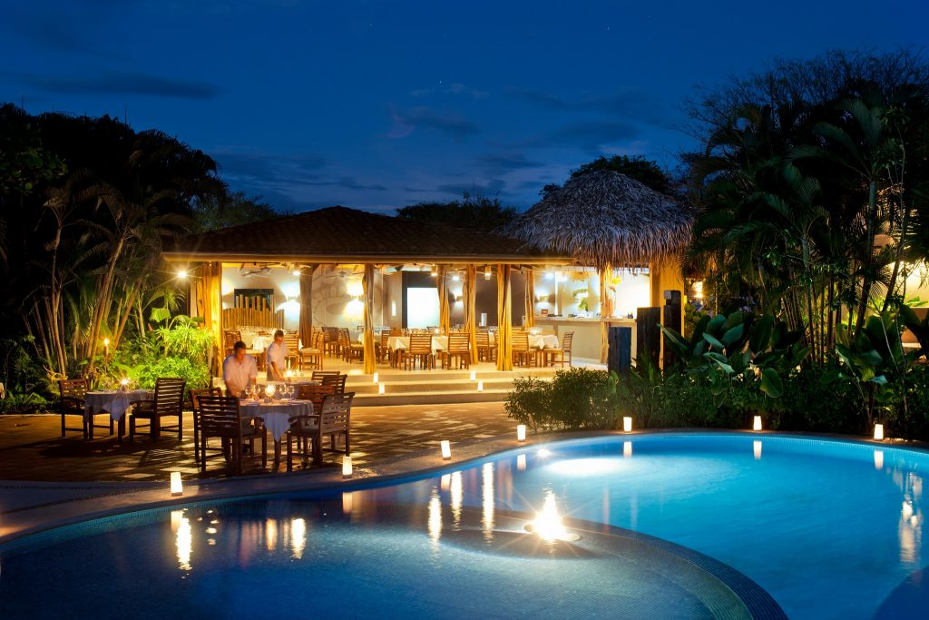 Cala Luna Boutique Hotel at night when the pool is lit and the dinner area is prepared