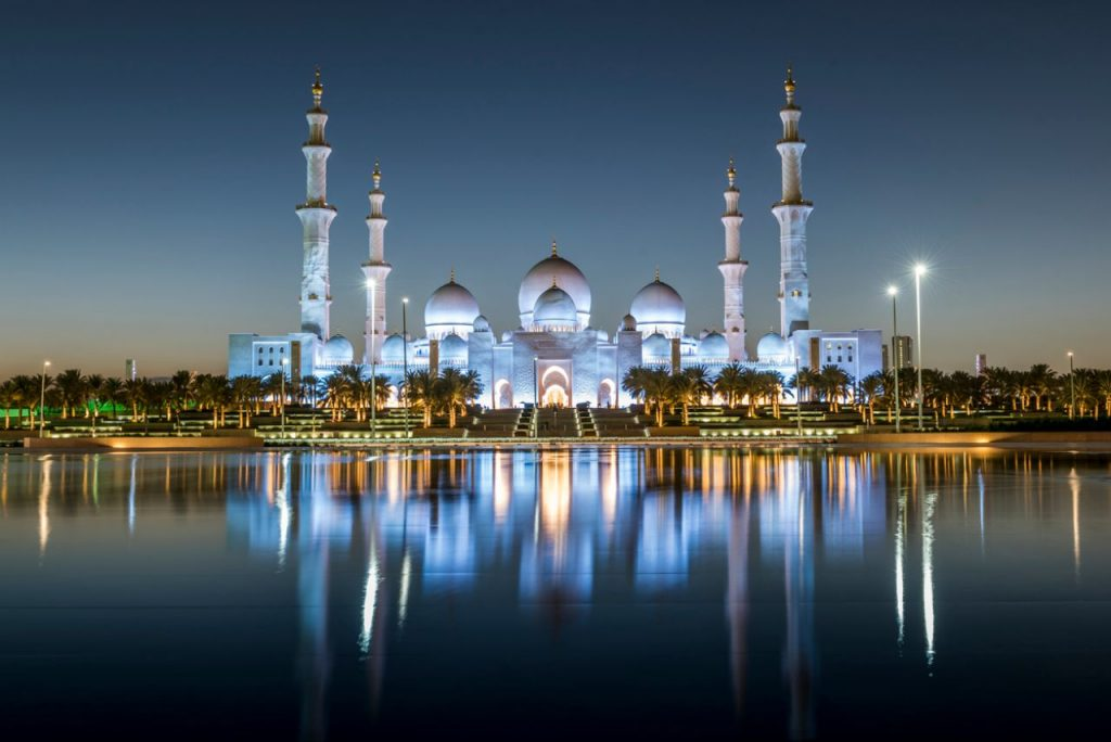 Abu Dhabi's Grand Mosque lit up at night time with reflections in the water