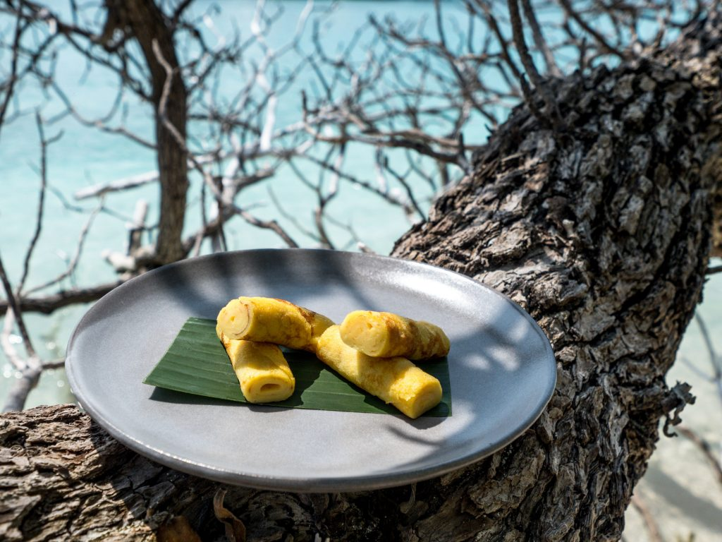 Crepes artfully presented on a blue plate and resting on a tropical tree in the Maldives