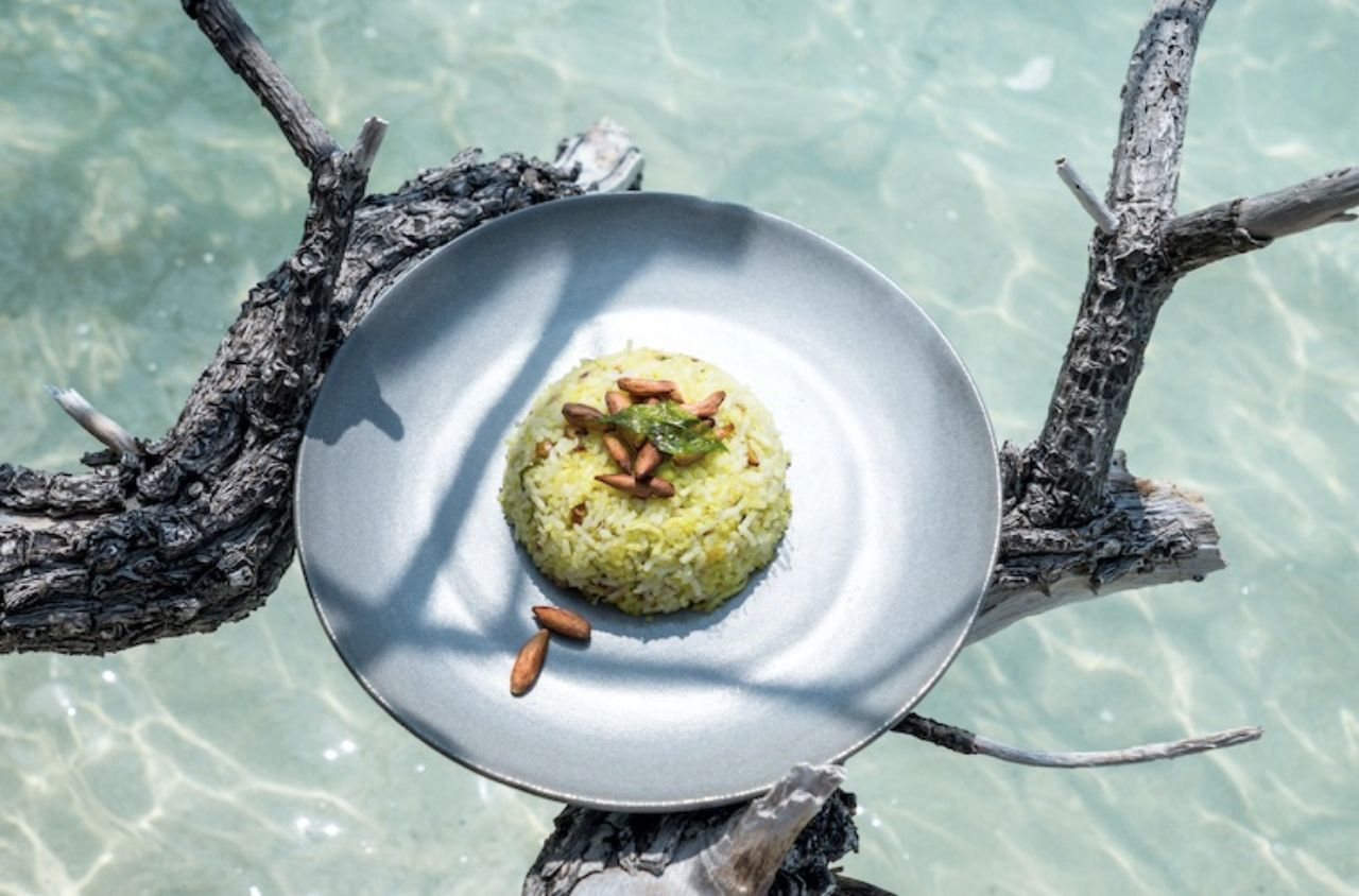Pine nut fried rice on a blue plate artistically photographeed over the ocean